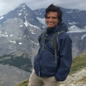 Image shows Erick standing in front of a mountain wearing a navy blue jacket and smiling