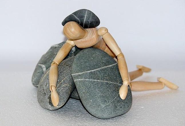 wooden man under rocks