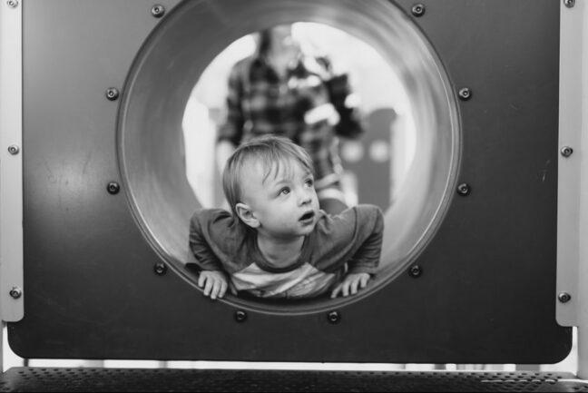 boy crawling through tube
