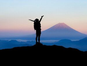 Person raising arms at mountain summit