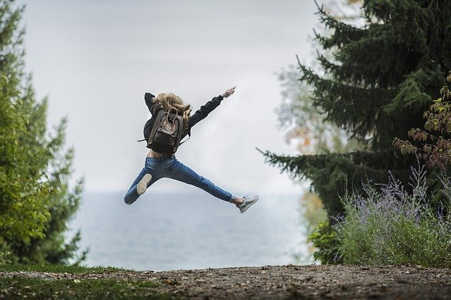 The backside of a woman wearing a jacket, jeans and a backpack jumping with one arm and leg outstretched in between trees with a body of water in the background.