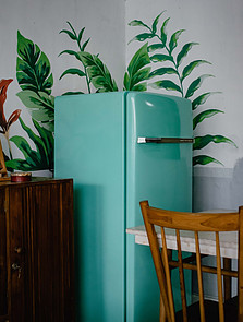 A blue retro fridge standing in a corner next to a counter and a table