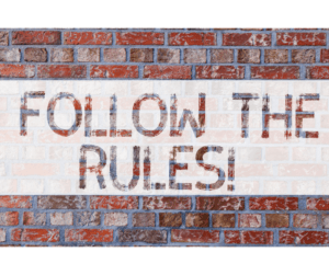 """Graphic of a brick wall with a text overlay saying """"FOLLOW THE RULES!"""""""