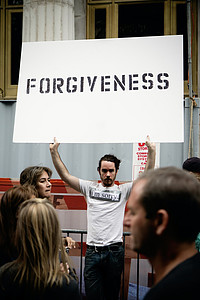 """Man holding a sign which says """"forgiveness"""""""