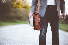 Bottom half of a man dressed in business casual with a leather bag and a book in his right hand