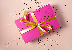 Gift with pink wrapping, a golden bow and golden confetti sprinkled over it