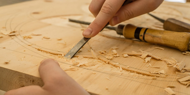 A pair of hands working on wood with a tool