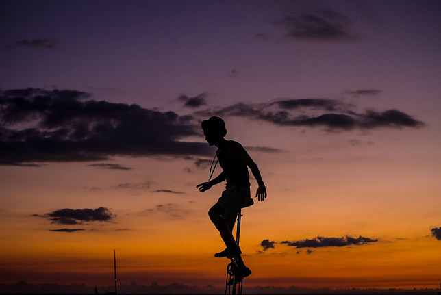 Image shows a black silhouette of a female on a unicycle in the foreground and a twilight sky in the background