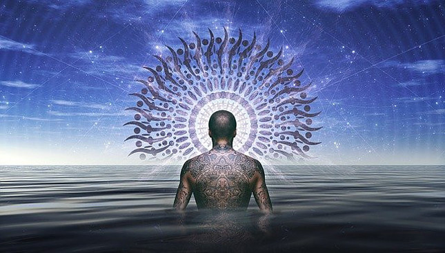 Image of a man with a tatooed back facing away standing waist deep in a body of water with a halo around his head in front of a dark blue sky