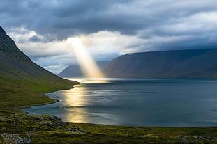 Beam of sunglight falling on a mountain lake through a cloudy sky