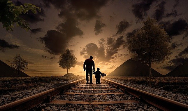 Image shows the silhouette of a grown man holding the hand of a little boy facing away while walking on train tracks